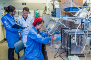 Professor and students work in a chemistry lab